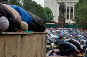 Kyrgyz Muslims pray in central Bishkek, with a monument of Soviet State founder Vladimir Lenin seen in the background, 25 June