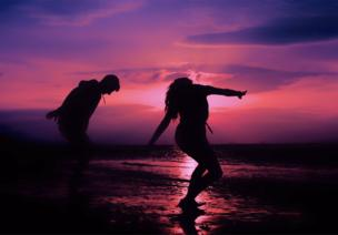 Two people dance under the pink sunset