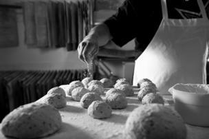 Un panadero espolvorea harina en unos panecillos