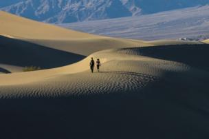 Una pareja camina sobre la arena.