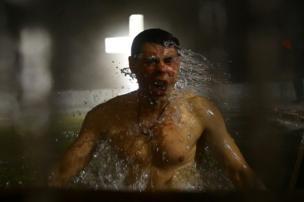 رجل يستحم بمياه ثلجية، خلال احتفالات المسيحيين الأرثوذكس بعيد الغطاس في مدينة مينسك في بيلاروسيا.