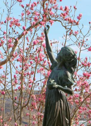 A sculpture of a girl in front of blossom