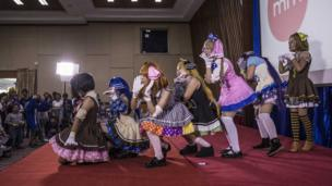 Seven women in cosplay dresses, line up behind one another, in pose, on stage