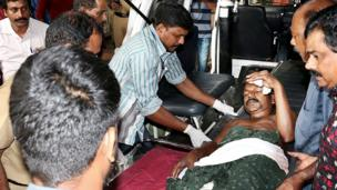 Indian medical officials and bystanders carry an injured man from a vehicle into a hospital in Paravur