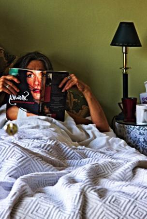 Una mujer lee en cama.