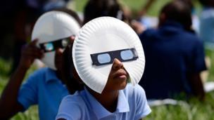 Missouri eyaletinin St Louis kentinde öğrenciler kendilerine dağıtılan gözlüklerle güneş tutulmasını izliyor.