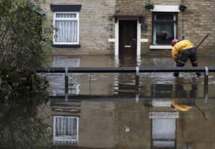 An emergency services worker stands in flood water in Stalybridge