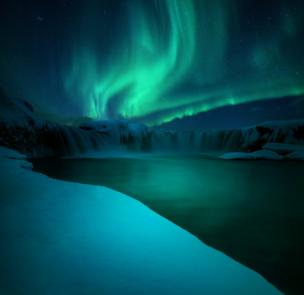 The northern lights over a waterfall