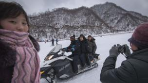 This photo taken on February 19, 2017 shows North Korean visitors posing on a snowmobile at the Masikryong ski resort,