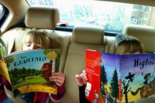 in_pictures Two children reading in back of car
