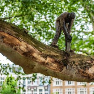 Sculpture of man sawing a branch