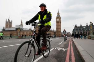 Pedestrians and a cyclist cross Westminster Bridge