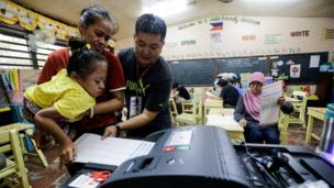 Fife Vanice Dayola, 21, who was born with bone misalignment, is carried by her mother Rowena Dayola and assisted by an election worker, as she casts her vote by inserting her ballot into a machine in a school polling station in Davao city, 9 May 2016