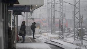 जर्मनी के म्यूनिख़ शहर में एक स्टेशन पर अपनी ट्रेन का इंतज़ार करते यात्री और दूर से बर्फ़ से ढकी पटरियों के बीच आती ट्रेन.