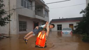 This picture taken on July 1, 2016 shows a boy being rescued from a flooded house in Xinzhou, in China's central Hubei province.