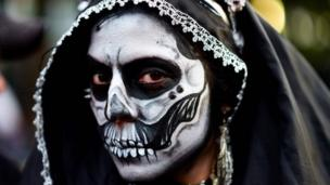 A woman wears a black hood and make-up during the Catrinas parade in Mexico City.