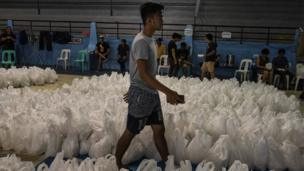 Volunteers prepare packed rice as aid to affected residents as Typhoon Mangkhut approaches on September 14, 2018 in Tuguegarao city, northern Philippines