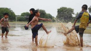 Niños jugando en un charco en Paraguay