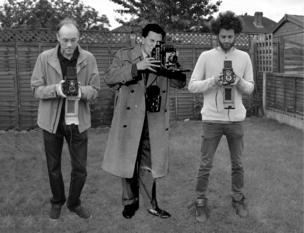 Tres generaciones de hombres con cámaras
