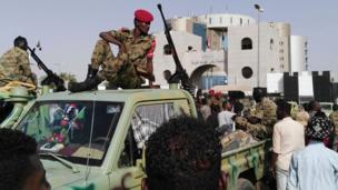 """جنود سودانيون أمام مقر عسكري، حيث تجمع متظاهرون يرون أن الإطاحة بالبشير """"انقلاب نفذه النظام"""""""