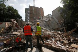 Rescue workers look at fellow workers searching for people under the rubble of a collapsed building