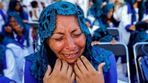 A woman with a blue mantilla cries with emotion during the annual gathering of the Light of the World church