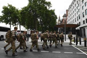 British soldiers arrive by bus and head toward a building next to New Scotland Yard police headquarters, in central London