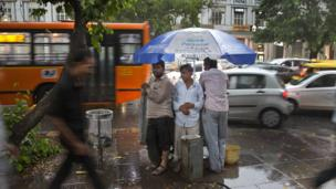 Indian commuters walk home in the rain as others take shelter under the umbrella of a mobile water drinking carriage in New Delhi, India, Monday, May 23, 2016.