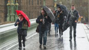 Pedestrians experience a brief snow shower on Westminster Bridge, in central London.