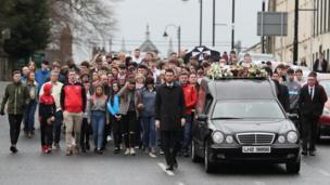 People walking behind the hearse carrying Morgan Barnard's coffin
