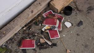 Playing cards that had been discarded after someone had tried to set to a board covering a window.