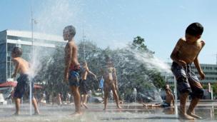 أطفال يلعبون بمضخات المياه في نافورة بقصر الأمم، خلال موجة الحر، في جنيف بسويسرا