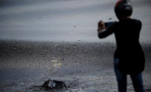 An Indian man takes photographs on his mobile phone of black oil as a thick oily tide from the sea lapped at the coast