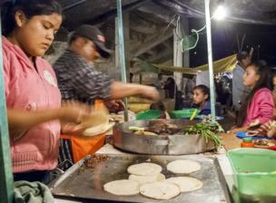 Señor preparando un taco en un mercado callejero iluminado apenas por una bombilla.