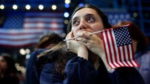 Una seguidora de Hillary Clinton se tapa la boca y mira hacia el horizonte en un evento programado de Hillary Clinton