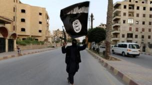 Member loyal ta tha Islamic State up in Iraq n' tha Levant (ISIL) waves a ISIL flag up in Raqqa on 29 June 2014.