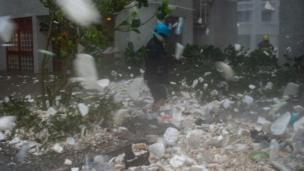 A photojournalist walks through plastic debris blown by strong winds during Super Typhoon Mangkhut in Heng Fa Chuen in Hong Kong on September 16, 2018.