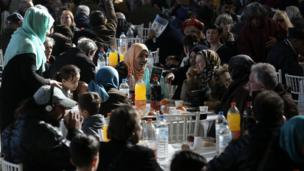 People in need and the homeless receive their annual Christmas meal provided by the City of Athens in an indoor stadium in Athens