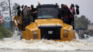 Un grupo de personas se sube a un camión de construcción para atravesar una zona inundada en Houston, Texas.