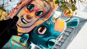 A man walks past a street art mural on the facade of a house in Fanzara near Castellon de la Plana