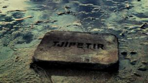 A rubber block engraved with the words Tjipetir washed up on a beach