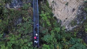 People climb on the newly-built metal ladder with hand railings to Atuler village on a cliff on November 11, 2016 in Zhaojue county, China.