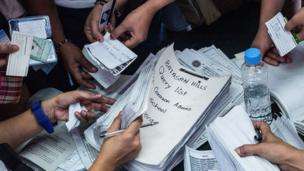People handing over names and IDs at a Manila polling station, to receive their ballots