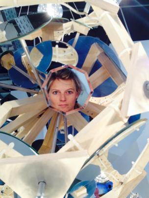 A woman's face is reflected through a mirror on an art installation