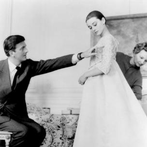 Givenchy and Audrey Hepburn in 1950s shot as she tries on a long-flowing, pale-coloured gown