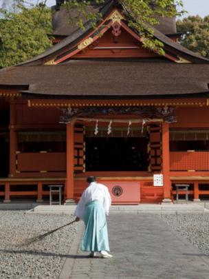 Tapınağın girişini temizleyen bir adam.