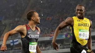 Usain Bolt y Andre de Grasse se sonríen mutuamente