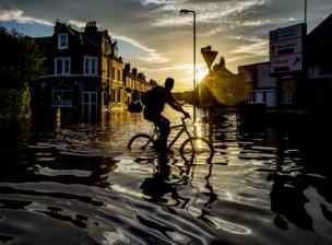 A cyclist travels through flood water along Warwick Road, Carlisle, Cumbria after severe flooding across the county.