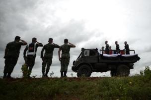 เจ้าหน้าที่ทหารแสดงความเคารพขณะขบวนเคลื่อนศพผ่าน