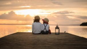 समुद्र किनारे बैठे दो बच्चे